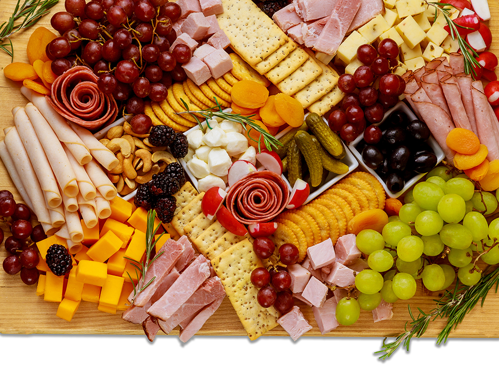 Hors d'Oeuvres Charcuterie board with selection of meats, cheeses, fruits, nuts, crackers, vegetables.